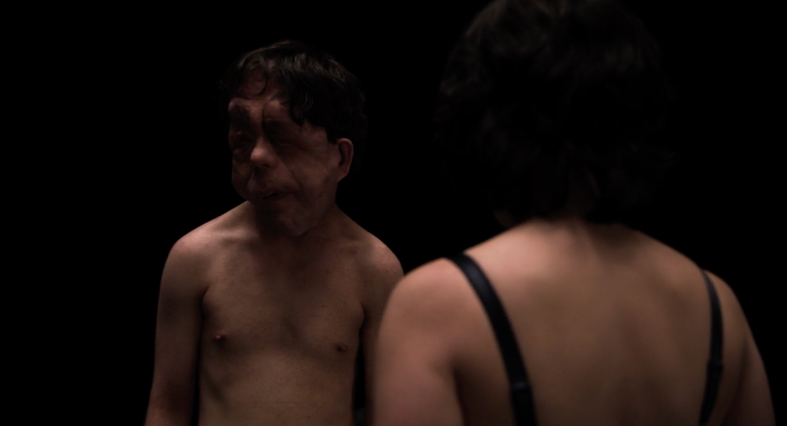 Scarlett Johansson and the disfigured man stand in the black room in Under the Skin