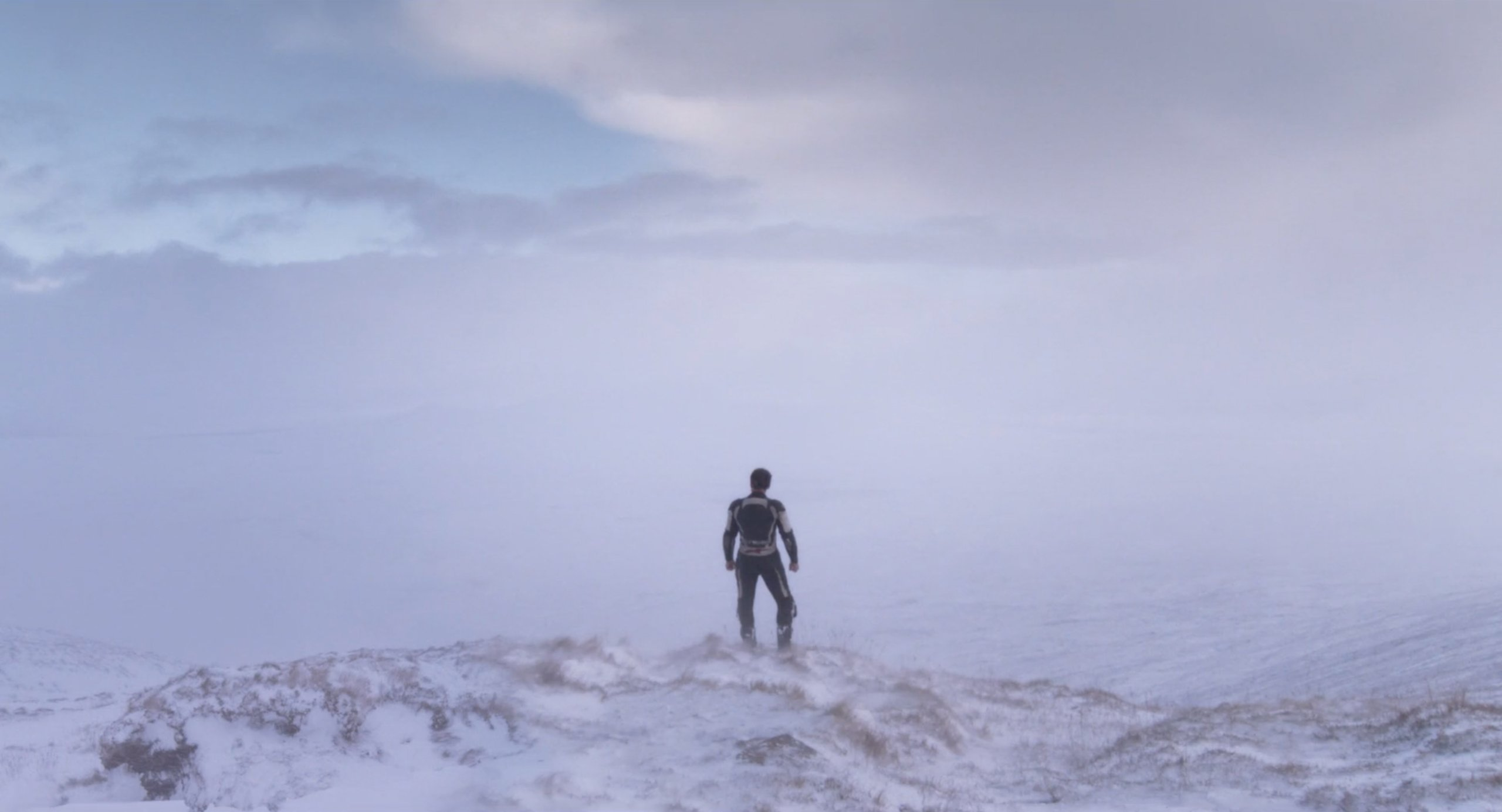 The Motorcycle Man looks over a snowy landscape while searching for The Woman in Under the Skin