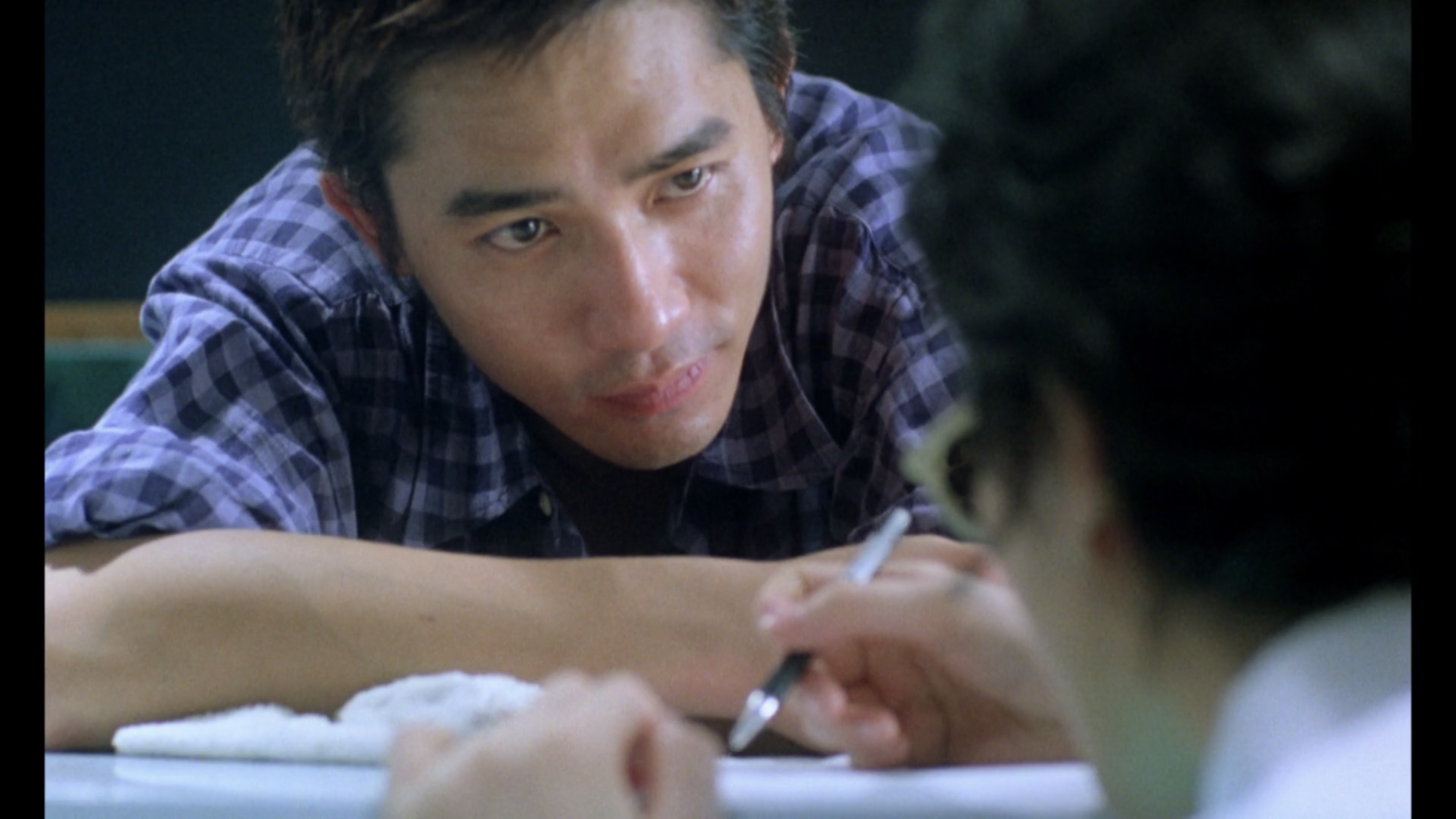 Cop 663 stares at Faye as she writes a boarding pass at the end of Chungking Express