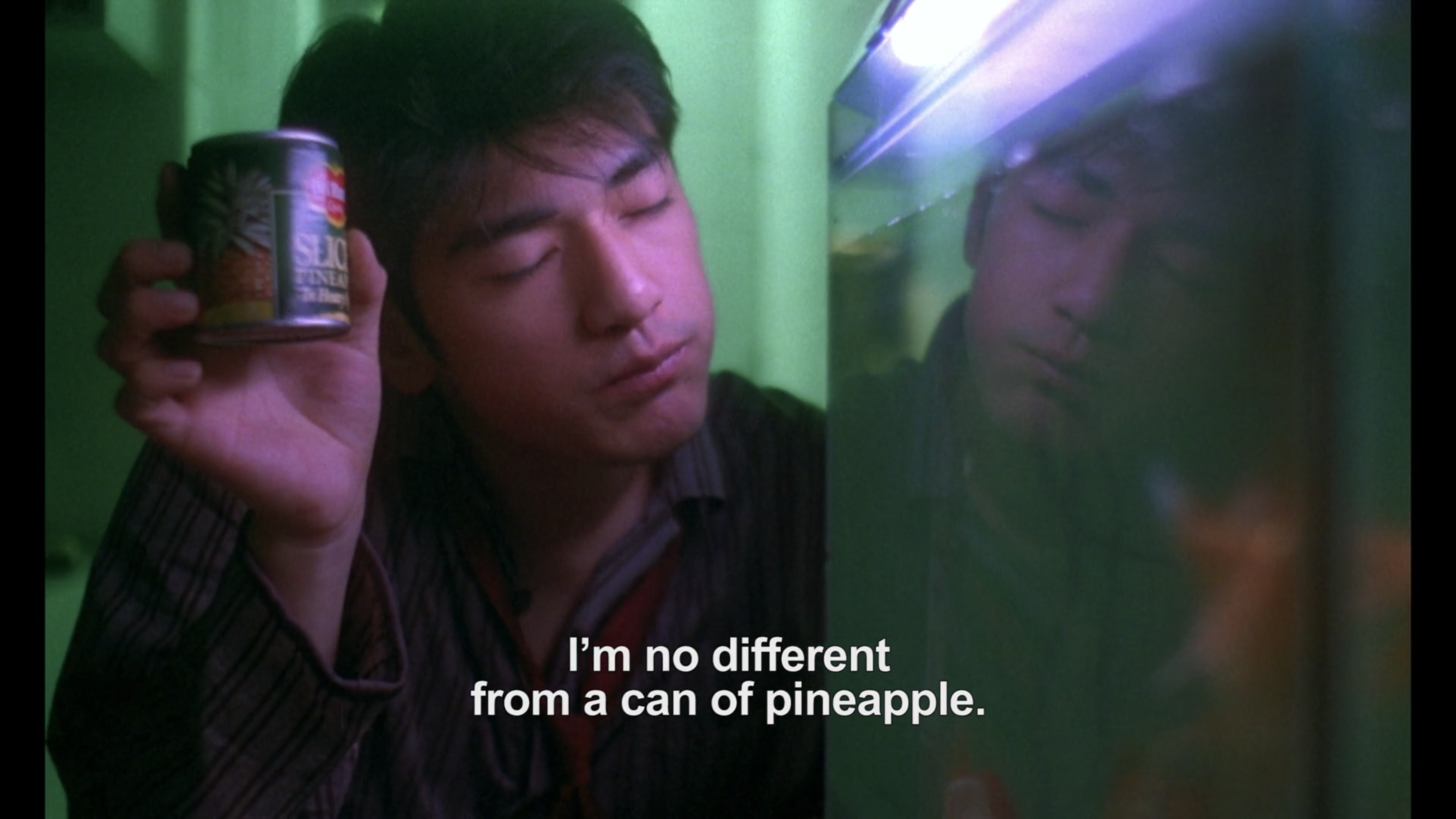 He Qiwu holds up a can of pineapple next to his fish tank in Chungking Express
