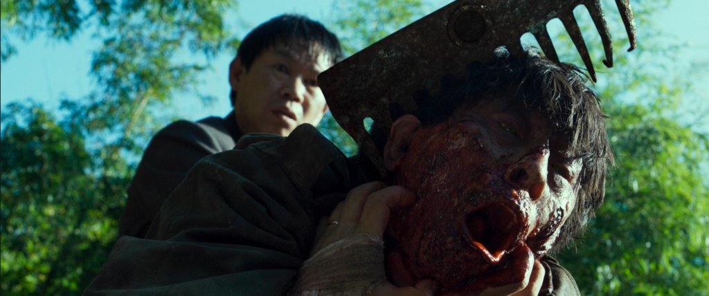 Park Choon-bae becomes a zombie and is stabbed in the head by a hoe in The Wailing