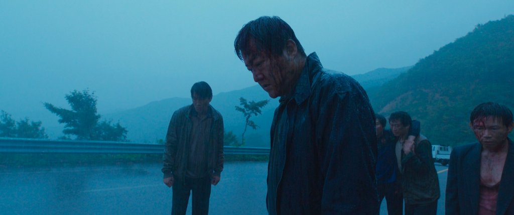 Jong-goo and his friends stare at the Japanese Stranger after hitting them with a car in The Wailing