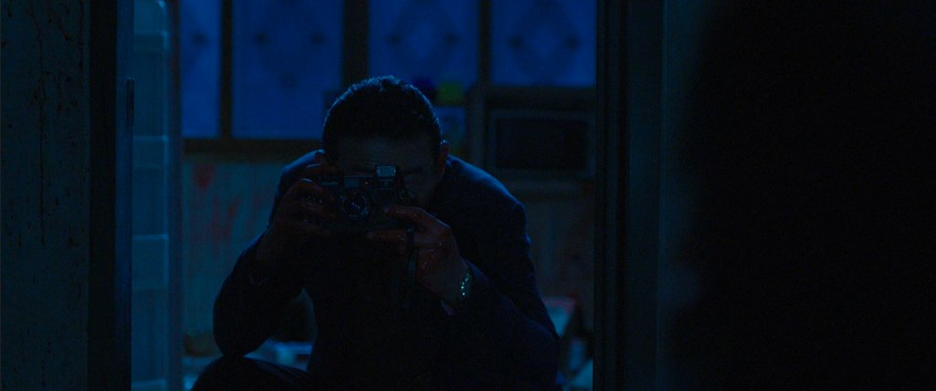 The Shaman takes a picture of Jong-goo at the end of The Wailing