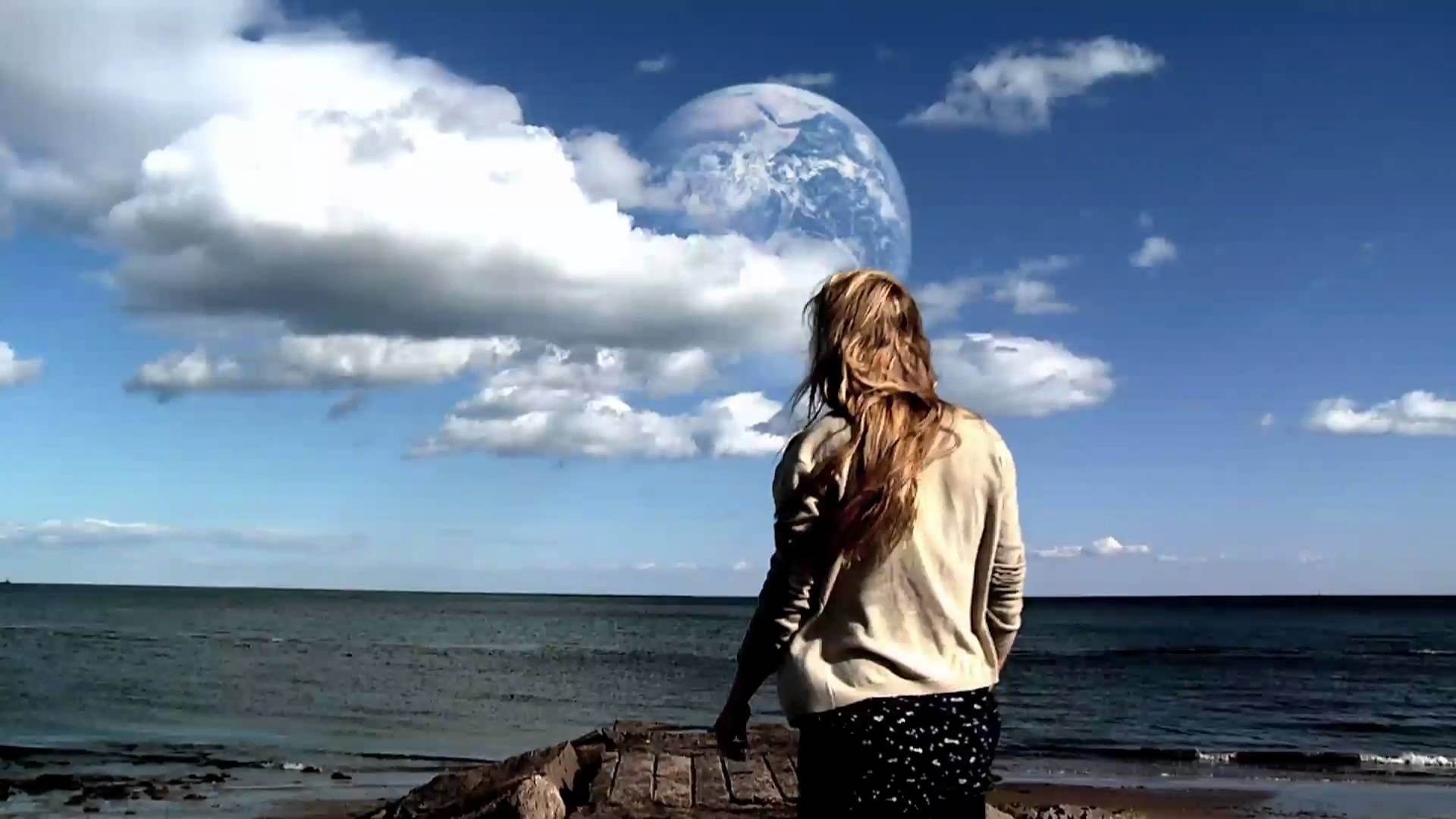Rhoda Williams (Brit Marling) stands near water and stares at a second Earth that's been discovered in Another Earth