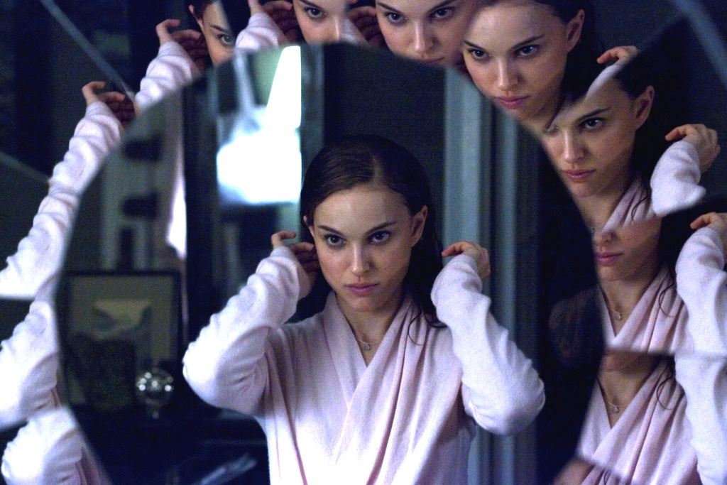 Nina Sayers (Natalie Portman) looks into the mirror and has multiple faces in Black Swan