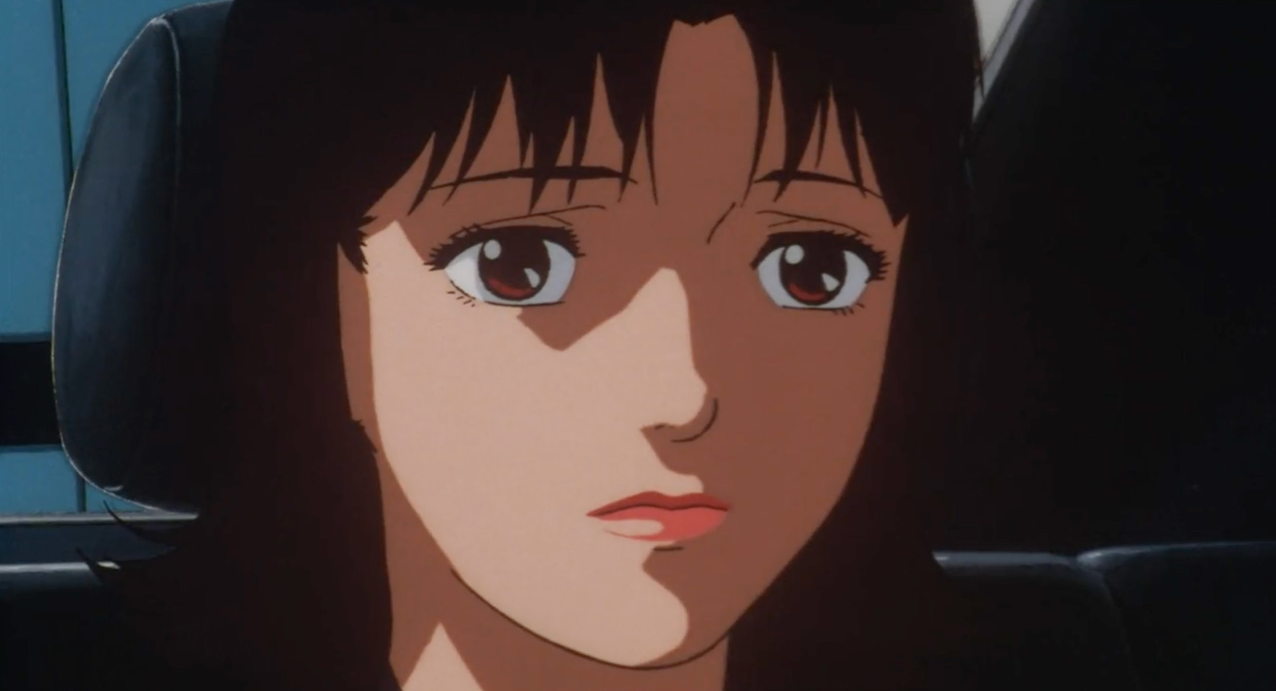 Mima sits in the back of a car looking sad in Perfect Blue