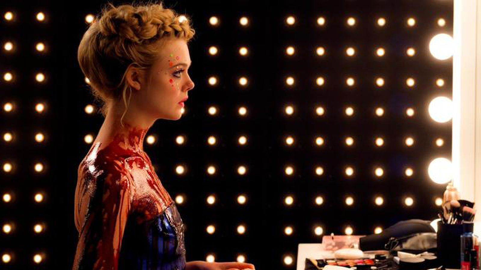 Jesse (Elle Fanning) looks into the mirror with lights surrounding her in The Neon Demon